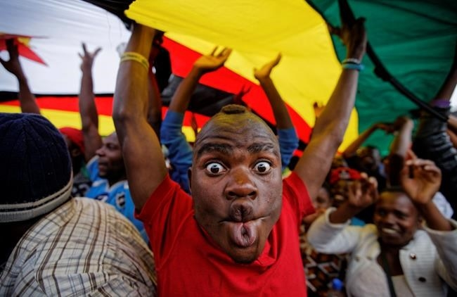 A happy protester pulls a face as he and others stand under a large national flag, at a demonstration of tens of thousands at Zimbabwe Grounds in Harare, Zimbabwe Saturday, Nov. 18, 2017.