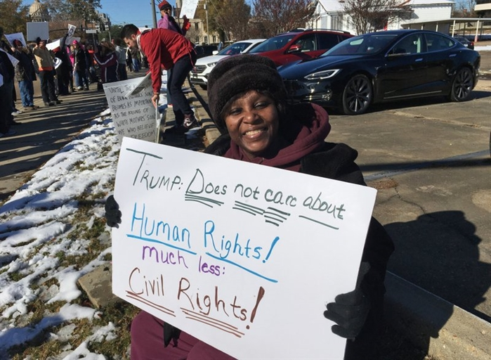 Gladys Bunzy of Jackson, Miss., protests Saturday, Dec. 9, 2017, against the visit of President Donald Trump in Jackson, Miss.