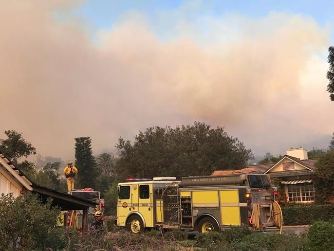 In this photo provided by the Santa Barbara County Fire Department, fire engines provide structure protection at the historic San Ysidro Ranch in Montecito, Calif., Saturday, Dec. 16, 2017.