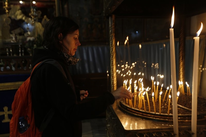 A Christian lights candles at the Church of the Nativity, built atop the site where Christians believe Jesus Christ was born, on Christmas Eve, in the West Bank City of Bethlehem, Sunday, Dec. 24, 2017.