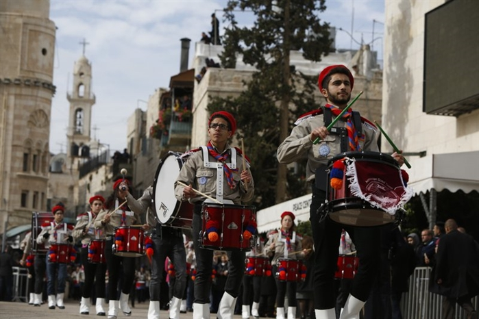 Members of a Palestinian marching band parade during Christmas celebrations outside the Church of the Nativity, built atop the site where Christians believe Jesus Christ was born, on Christmas Eve, in the West Bank City of Bethlehem, Sunday, Dec. 24, 2017.