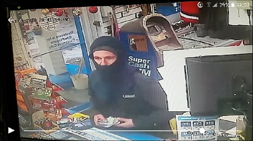 Still shot of a suspect demanding money from an employee at Super Save Gas on Jan. 1, 2018.