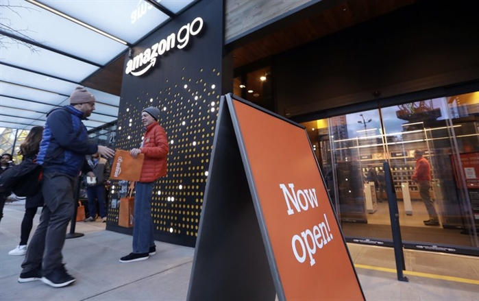 A customer is handed a complimentary shopping bag as he heads into an Amazon Go store, Monday, Jan. 22, 2018, in Seattle.