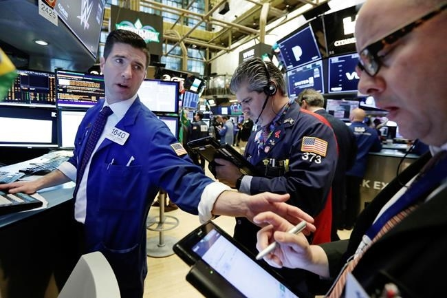 Specialist Thomas McArdle, left, works with traders John Panin, center, and Jeffrey Vazquez on the floor of the New York Stock Exchange, Monday, April 2, 2018. U.S. stocks are skidding Monday morning after China raised import duties on U.S. pork, apples and other products.