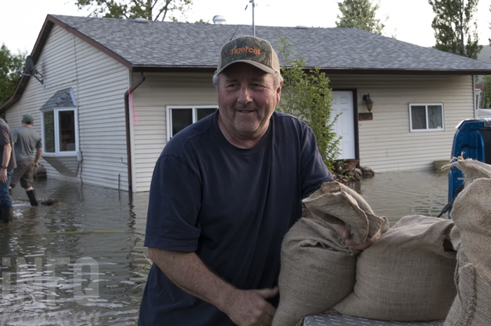 Bill Pierce grabs a sandbag. Behind him the neighbours house stands submerged in water.