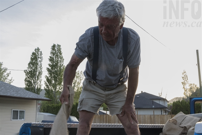 Bruce Mynott passes sandbags from the pickup truck.