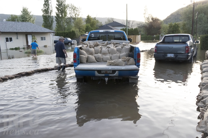 Mynott drives the blue pickup truck full of sandbags. Volunteers have been filling them at the Merritt Civic Centre.