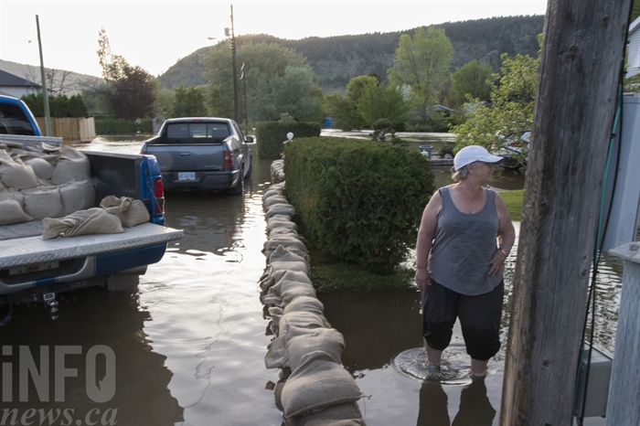 Mischelle stands in the neighbour's yard as family friend Bruce Mynott starts the truck full of sandbags in the back to take to the Pierce house across the street.