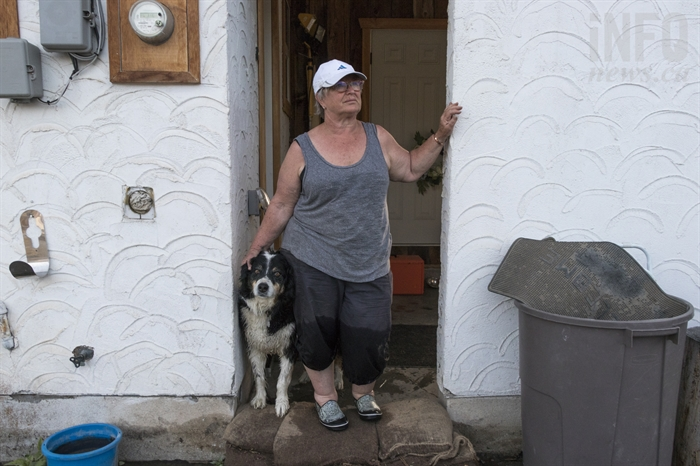 Mischelle Pierce stands with her dog Dexter on top of the sandbags they have been putting in front of their house to stop the flooding on Sunday, May 13, 2018. Pierce and her husband, Bill Pierce, are one of the households in Merritt, B.C. affected by flooding