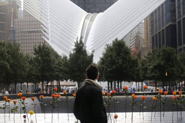 A man looks at the North Pool at the World Trade Center during a ceremony marking the 17th anniversary of the terrorist attacks on the United States. Tuesday, Sept. 11, 2018, in New York. In the background is the World Trade Center Transportation Hub.