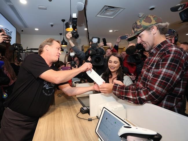 Canopy Growth CEO Bruce Linton, left to right, provides the receipt for the first legal cannabis for recreation use sold in Canada to Nikki Rose and Ian Power at the Tweed shop on Water Street in St. John's N.L. at 12:01 am NDT on Wednesday October 17, 2018.