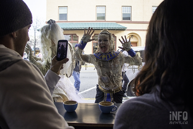 A couple of patrons at Zack's Coffee take a picture of a mummy-inspired zombie staring at them through the window.
