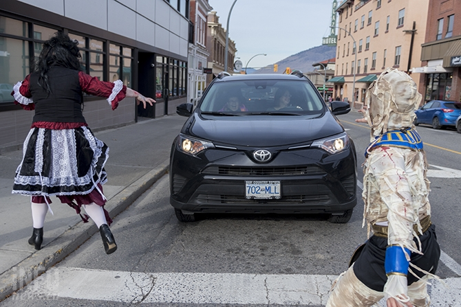 Two people in a car are surrounded by zombies crossing the street.