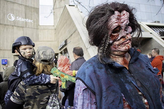 Chevonne Oginski and her son Owen, 3, crashed the march dressed as zombie hunters. Chevonne holds Owen as he watches Una Connor walk by in costume.