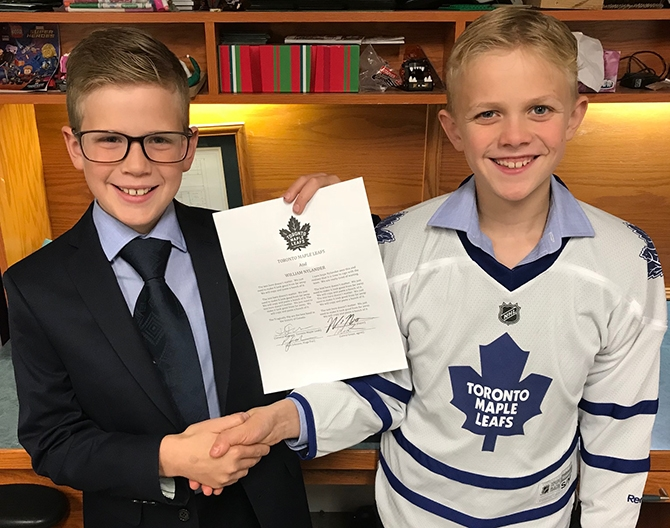 Toronto Maple Leaf fans Rhys, left, and Ryder Johnson hope there will be smiling faces and a contract in real life soon.