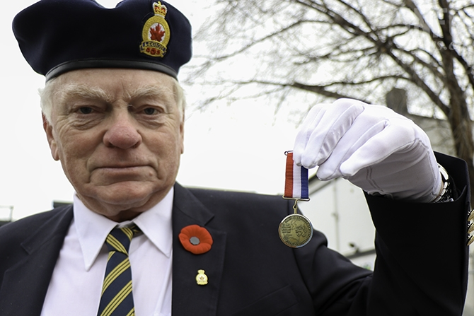 Peter Miedema, who sang 'O Canada' at the ceremony, shows his father's medal who was a member of the Allied underground in the Netherlands. The red, white, and blue symbolize the Dutch flag and the medal represents the 50th anniversary of the 1945 liberation of the Netherlands.