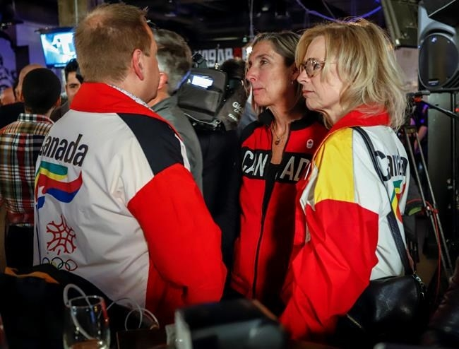Dave King, left, Linda King, right, son and daughter of Frank King, wearing 1988 Calgary Olympic jackets react to the results of a plebiscite on whether the city should proceed with a bid for the 2026 Winter Olympics, in Calgary, Alta., Tuesday, Nov. 13, 2018.