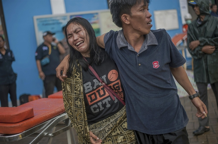 A woman reacts after identifying a relative among the bodies of tsunami victims in Carita, Indonesia, Sunday, Dec. 23, 2018. The tsunami occurred after the eruption of a volcano around Indonesia's Sunda Strait during a busy holiday weekend, sending water crashing ashore and sweeping away hotels, hundreds of houses and people attending a beach concert.