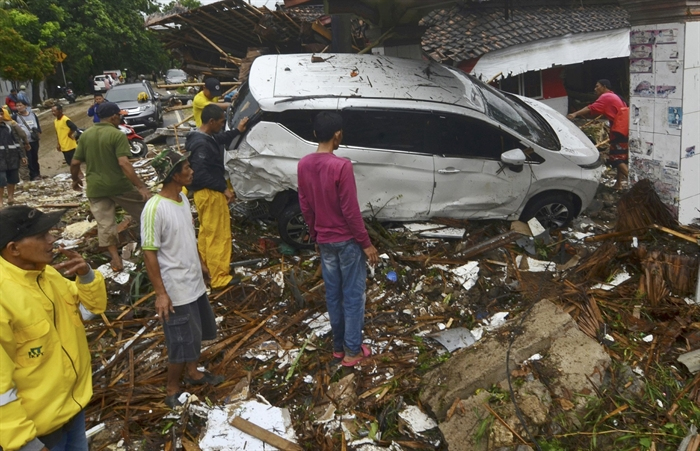 People inspect the wreckage of a car swept away by a tsunami in Carita, Indonesia, Sunday, Dec. 23, 2018. The tsunami occurred after the eruption of a volcano around Indonesia's Sunda Strait during a busy holiday weekend, sending water crashing ashore and sweeping away hotels, hundreds of houses and people attending a beach concert.