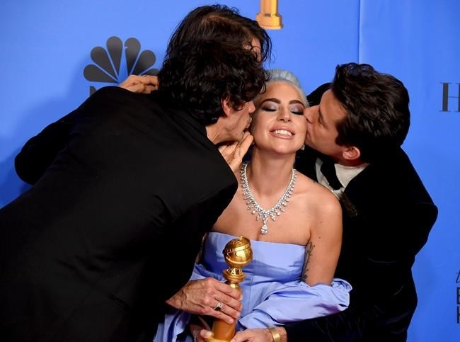 Anthony Rossomando, from left, Andrew Wyatt, and Mark Ronson, right, kiss Lady Gaga, second right, as they pose in the press room with the award for best original song, motion picture for