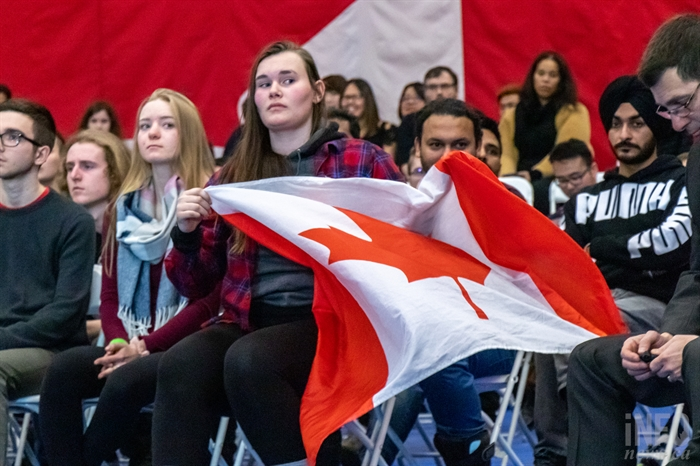 A woman waves a Canadian flag as she sits in the front row of Justin Trudeau's town hall meeting at TRU on Wednesday, Jan. 9, 2019.