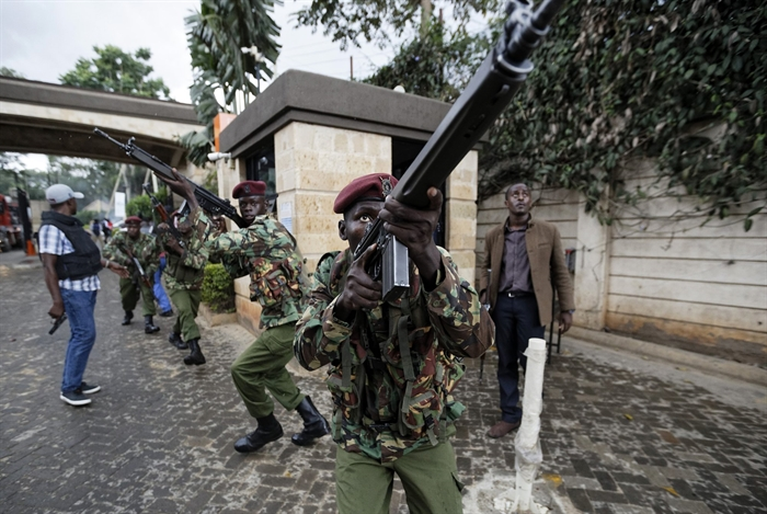 Kenyan security forces aim their weapons up at buildings as they run through a hotel complex in Nairobi, Kenya Tuesday, Jan. 15, 2019. Terrorists attacked an upscale hotel complex in Kenya's capital Tuesday, sending people fleeing in panic as explosions and heavy gunfire reverberated through the neighborhood.