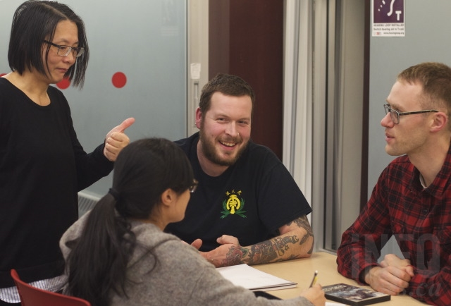 Marriana Chen, left, checks in on Mandarin language learners Luke Mortenson, centre, and Brendan Ferguson.