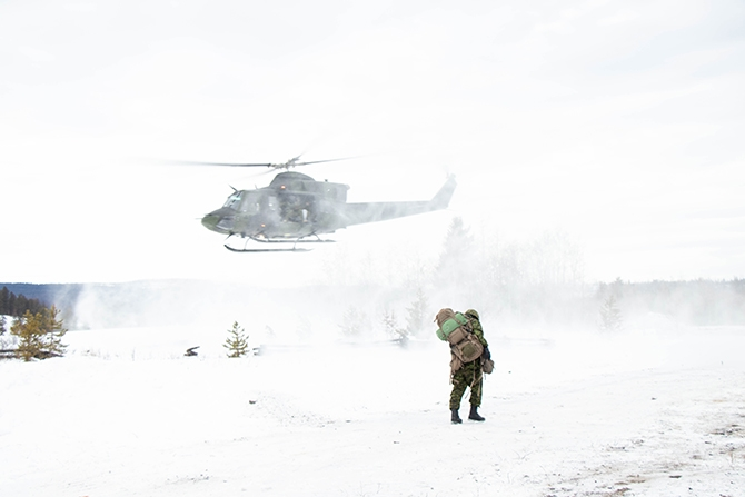 The helicopter creates formidable winds as it lifts off from the ground. It is not snowing but the force from the blades kicks up snow and blows it for several meters as a soldier walks towards the landing zone.