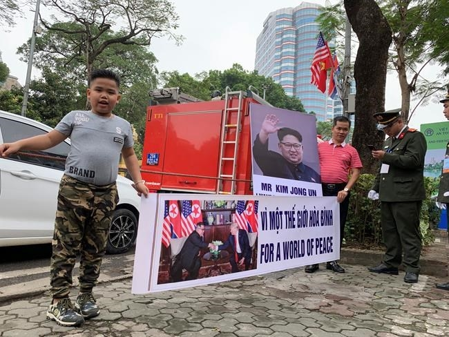 Pham Quang Dung, 8, wearing a hairstyle of North Korean leader Kim Jong Un, holds a placard that reads