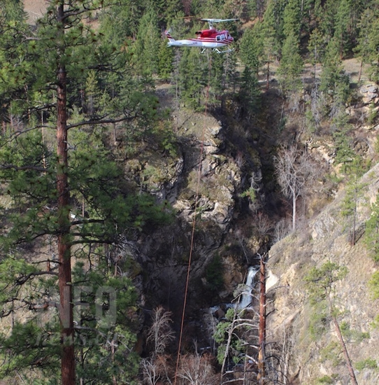 Hardy Falls can be seen in the background as a helicopter airlifts a prefabricated wooden bridge, Thursday, April 11, 2019.