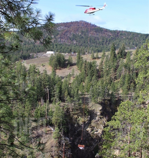 A helicopter airlifts a wooden prefabricated bridge in Hardy Falls Provincial Park, Thursday, April 11, 2019.