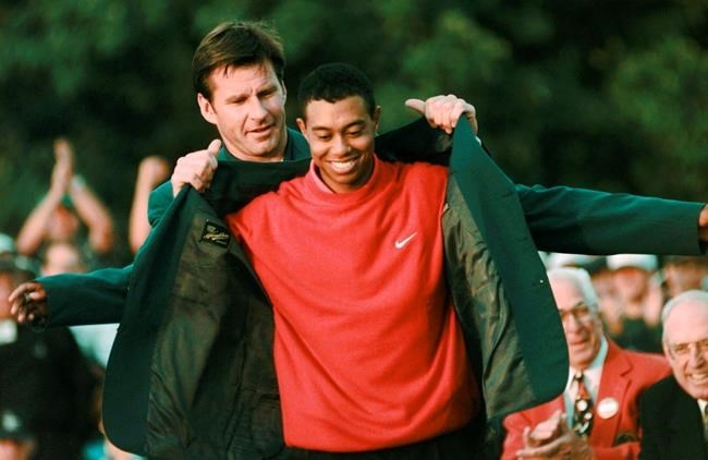 FILE - In this April 13, 1997, file photo, Masters champion Tiger Woods receives his Green Jacket from last year's winner Nick Faldo, rear, at the Augusta National Golf Club in Augusta, Ga. Woods completes an amazing journey by winning the 2019 Masters, overcoming 11 years of personal foibles and professional pain that seemed likely to be his lasting legacy.