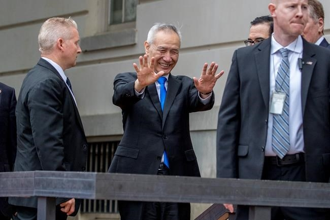 Chinese Vice Premier Liu He, center, waves to members of the media as he arrives at the Office of the United States Trade Representative in Washington, Friday, May 10, 2019 for trade talks between the United States and China.