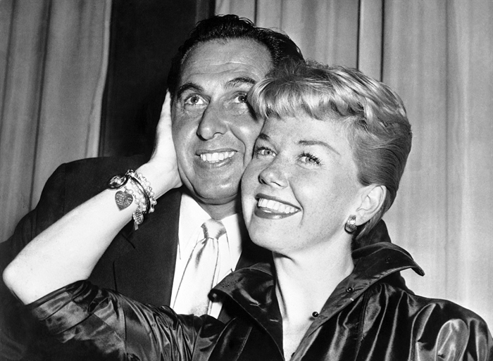 FILE - In this April 12, 1955 file photo, film actress and singer Doris Day poses with her husband and agent Martin Melcher at their hotel after arriving in London. Day, whose wholesome screen presence stood for a time of innocence in '60s films, has died, her foundation says. She was 97. The Doris Day Animal Foundation confirmed Day died early Monday, May 13, 2019, at her Carmel Valley, California, home.
