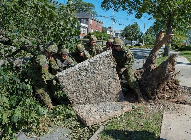 Members of the 4 Engineer Support Regiment from Canadian Forces Base Gagetown move a slab of sidewalk as they assist in the cleanup in Halifax on Monday, Sept. 9, 2019. Hurricane Dorian brought wind, rain and heavy seas that knocked out power across the region.