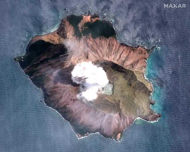 In this satellite image taken and released on Dec. 12, 2019, by Maxar Technologies steam rises from the volcano on White Island off the coast of Whakatane, New Zealand. A New Zealand island volcano vented more steam and mud Wednesday in an increase of geothermal activity that again delayed the recovery of victims' bodies from a deadly eruption two days ago.