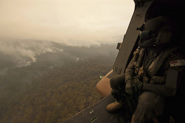 In this Sunday, Jan. 5, 2020, photo provided by Australian Department of Defence, a Royal Australian Navy MRH-90 helicopter crew member looks out over fires burning near Cann River, Australia. The wildfires have so far scorched an area twice the size of the U.S. state of Maryland.