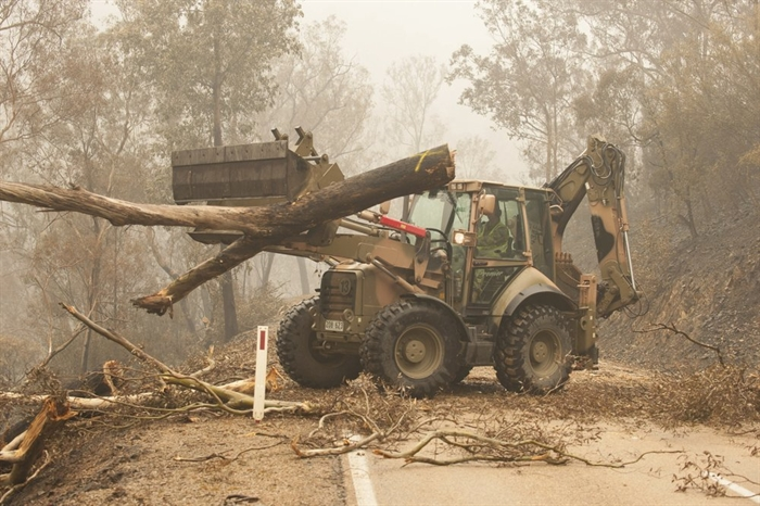 "In this image released and dated on Jan. 6, 2020, from Australian Department of Defence, plant operators Cpl. Duncan Keith and Sapper Ian Larner of the 22nd Engineer Regiment use a 434 backhoe to assist staff from Forestry Management Victoria to clear fire damaged trees from the great Alpine road between Bairnsdale and Omeo during Operation Bushfire Assist 19-20 in Bairnsdale, Victoria, Australia. Australia's government on Monday said it was willing to pay ""whatever it takes"" to help communities recover from deadly wildfires that have ravaged the country."