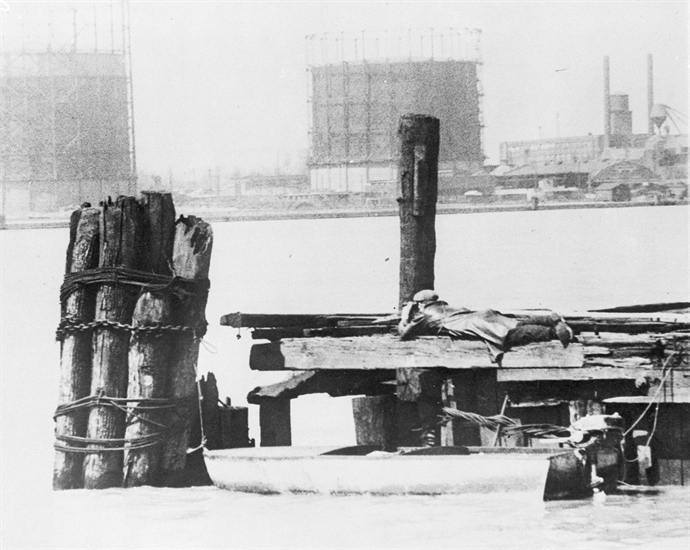 FILE - In this April 28, 1929, file photo a rum runner in Windsor, on the Canadian side of the Detroit River, watches with field glasses for lookout on the American side to signal that no prohibition agents are in sight. His outboard motorboat, loaded with illegal liquor, is shown beneath pilings.