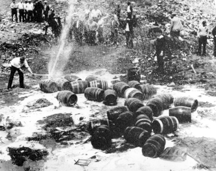 FILE - In this June 18, 1931, file photo beer barrels are destroyed by prohibition agents at a dump in New York City. The federal government, as well as state and local authorities, spent huge sums on enforcement yet never allocated sufficient resources to do the job effectively. Bootleggers awash in cash bribed judges, politicians and law enforcement officers to let their operations continue.