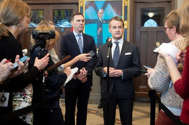 Minister of Finance Bill Morneau looks on as Natural Resources Minister Seamus O'Regan responds to a question from the media in Ottawa, Tuesday, February 4, 2020.