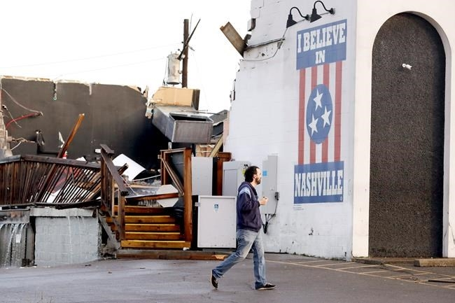 A man walks by The Basement East, a live music venue destroyed by storms Tuesday, March 3, 2020, in Nashville, Tenn. Tornadoes ripped across Tennessee early Tuesday, shredding buildings and killing multiple people.