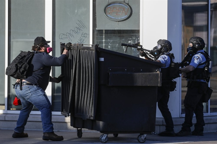 A protestor faces off with two police officers using less-lethal ammunition in their weapons, Thursday, May 28, 2020, in St. Paul, Minn. Protests over the death of George Floyd, a black man who died in police custody Monday, broke out in Minneapolis for a third straight night.