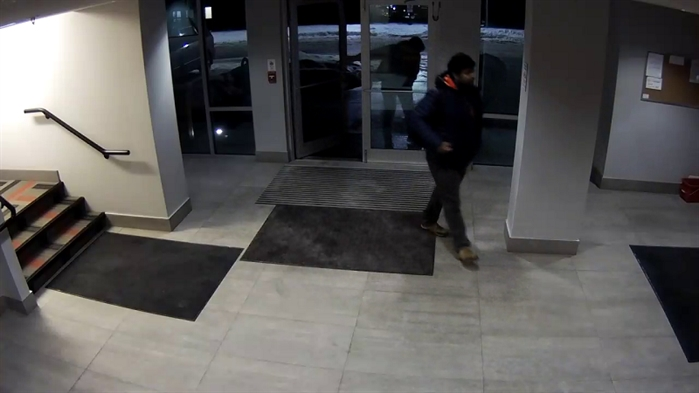 The second unknown man is described as; dark skinned, with dark hair and facial hair, wearing a dark coloured (possibly blue) winter jacket, with an orange lined hood and a dark coloured backpack. This man is seen in the photo entering the lobby through the glass doors.