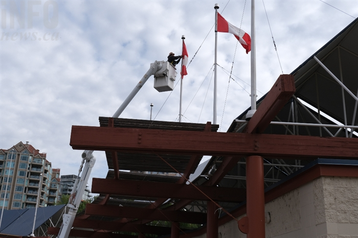 A Kelowna city worker removes a Canadian flag at Tugboat Bay.