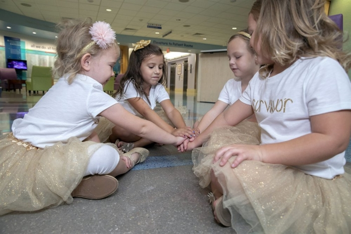 In this photo provided by Johns Hopkins All Children's Hospital, Lauren Glynn, Chloe Grimes, McKinley Moore and Avalynn Luciano place their hands together at the hospital in St. Petersburg, Fla., Aug. 9, 2018. The girls, who were diagnosed with cancer in 2016 and became fast friends while undergoing treatment, reunite every year.