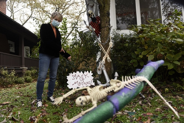 Carol McCarthy poses next to pirate-themed Halloween decorations reminding people to mask up while trick-or-treating during the COVID-19 pandemic, Monday, Oct. 26, 2020, in Palmyra, N.J.
