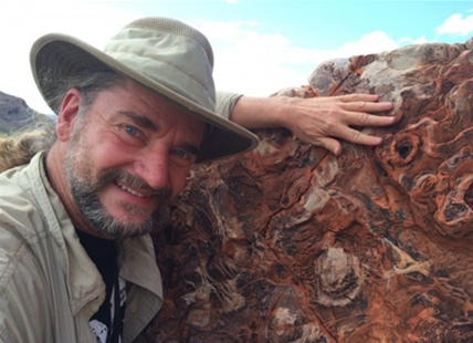 Dr. Bruce Damer standing with a 3.5-billion-year-old sedimentary rock he studied while researching the origin of life in Western Australia.