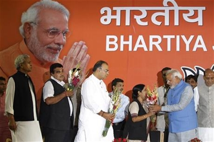 Opposition Bharatiya Janata Party (BJP) leader and India's next prime minister Narendra Modi, second right, receives flowers from party leader Sushma Swaraj, as Arun Jaitley, center, and Nitin Gadkari, second left, wait their turn, at the party headquarters in New Delhi, India, Saturday, May 17, 2014.