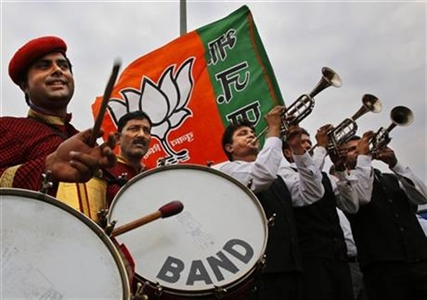 Members of an Indian band perform outside the airport as they wait for the arrival of Bharatiya Janata Party leader and India's next prime minister Narendra Modi in New Delhi, India, Saturday, May 17, 2014.